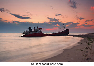 Ship after wreck on the coast during colorful sunset