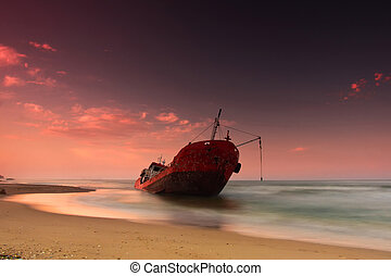 Ship after wreck on the coast with  colorful pink  sunset