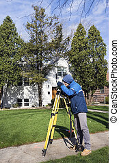 Surveyor working with theodolite in residential area