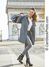happy young fashion-monger in trench coat in Paris, France -...