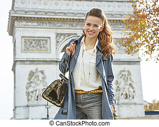 happy young elegant woman in trench coat in Paris, France -...