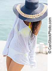 Young woman in bikini and beach hat at the beach