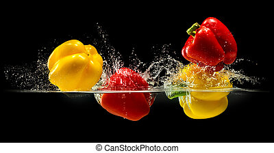 Group of bell pepper falling in water with splash on black...