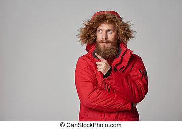 Pensive bearded man in red winter jacket - Bearded man in...
