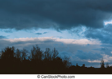 storm clouds over the forest gloomy sky over silhouette of...