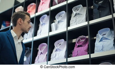 Man chooses a shirt at store - Man looking at a shirts at...