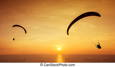 Two silhouettes of skydivers are flies on background sunset...