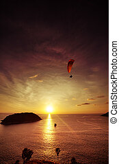 Skydiver flies over the sea on the background of sunset...
