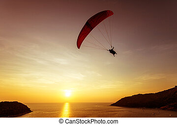 Silhouette of skydiver flies on background sunset sky and...