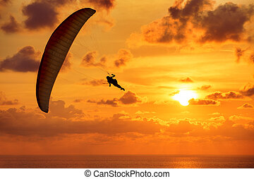 Silhouette of skydiver on sunset and the sea - Silhouette of...