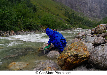 man prospector panning gold on a river with sluice box  rainy day
