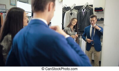 Assistant helps to a customer choose a tie - Assistant woman...