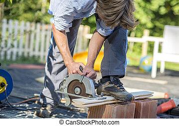 Man cutting boards with a circular saw - Unidentifiable...