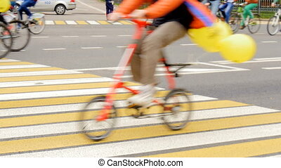 Many people are riding bicycles on city streets. - Many...