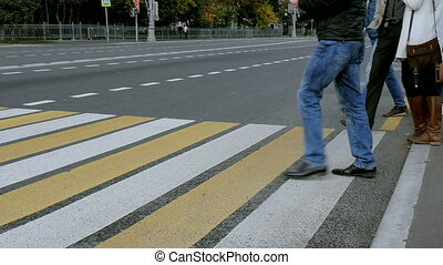 People crossing the street at a pedestrian crossing. City...