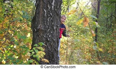 a cute child peeks from behind a tree in the Park