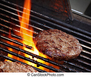 Barbeque - Burger pattie on a barbecue with flames