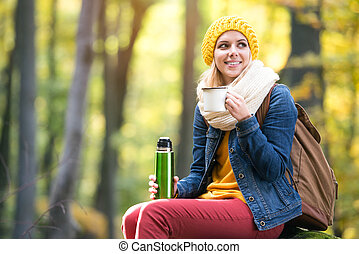 Beautiful woman in autumn forest, thermos and cup -...