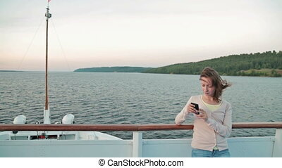 Young beautiful woman standing on deck of cruise ship and using her smart phone
