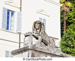 Stone lion guarding door, house on the back, horizontal...