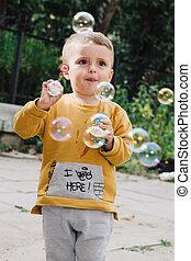 Boy blowing bubbles - Portrait of cute little blond boy...