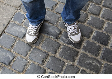Teenage legs in sneakers and blue jeans standing on paving stones, top view, unusual perspective