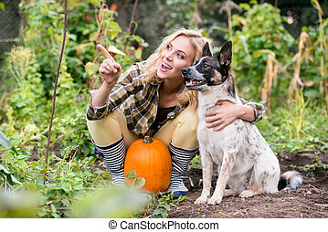 Young blond woman with dog harvesting pumpkins, autumn...