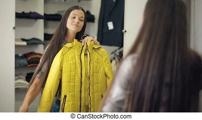 Woman trying on clothes - woman trying on jacket at store in...