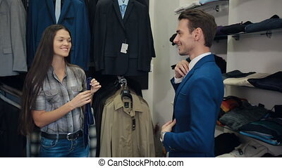 Man choosing a tie with a assistants help - Assistant woman...