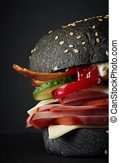 Gourmet black burger with Spicy sauce on black background