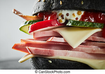 Burger with ham and black bun, with lettuce and mayonnaise...