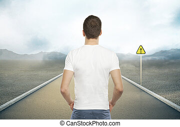 Success concept - Casual young man standing on road with...