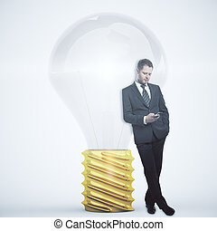 Idea concept - Businessman using smartphone while leaning on...