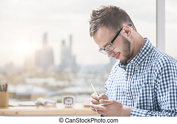 Sideview of young man taking notes