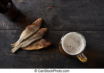 dried fish and beer on a table - dried fish and beer on a...