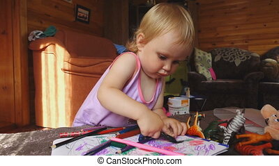 Sweet little girl draws with colored pencils