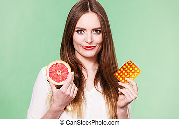 Woman holds grapefruit and pills blister pack vitamin c -...