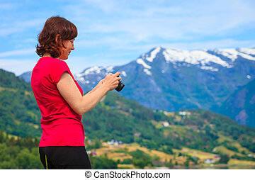 Tourist taking photo at norwegian fjord - Tourism vacation...