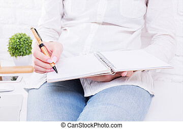 Woman writing in notepad - Closeup of woman in jeans and...