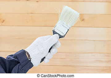 Hand in glove cotton holding brush paints with wall wood...