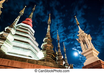 Night view of a temple in Chiang Mai, Thailand, with clouds...