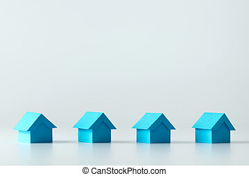 Real estate industry - Blue model houses in a row for real...