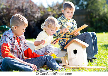 Kids boys play and build birdhouse sitting on green grass -...