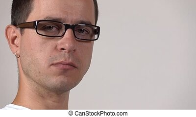 Portrait of serious programmer in black rim glasses against...