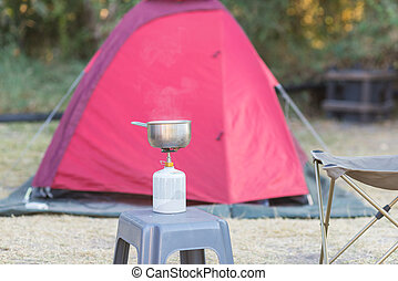 Cooking with gas stove in camping site. Selective focus on gas burner, pot and smoke from boiling water. Tent in the background out of focus. Outdoor activities.