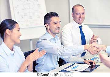 smiling business team shaking hands in office - business,...