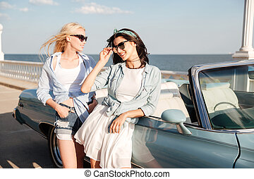 Two beautiful young women standing near cabriolet on...