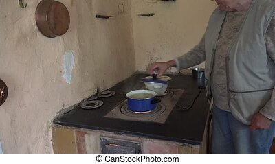 senior woman cook in pots on old furnace stove in rural kitchen. 4K