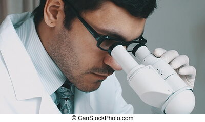 Young scientist looking through the microscope - Closeup of...
