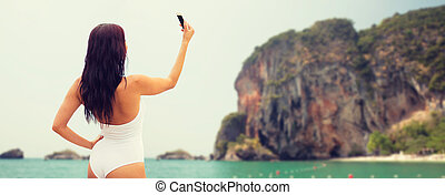 young woman taking selfie with smartphone on beach - summer,...
